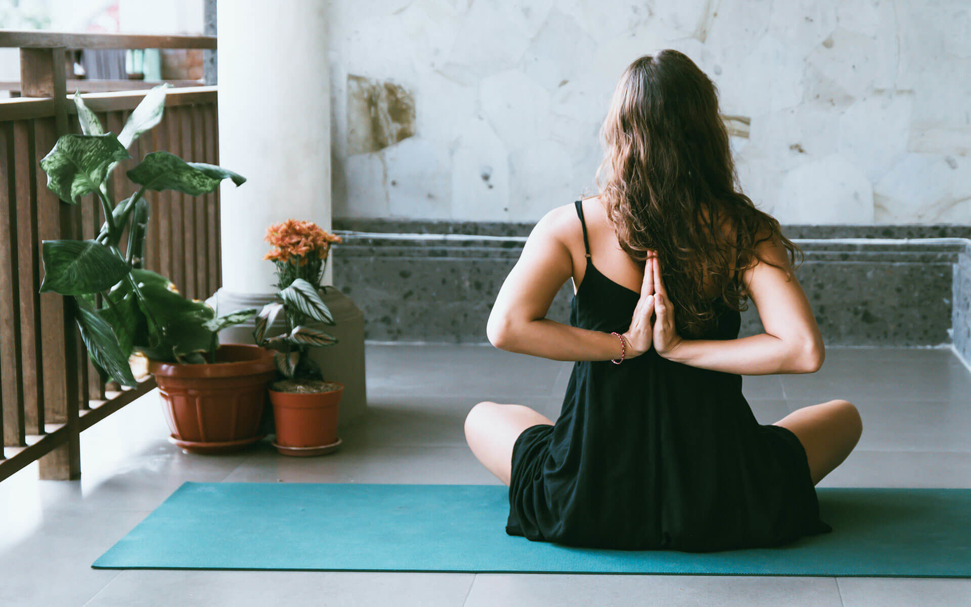 woman wearing black doing yoga next to potted plants