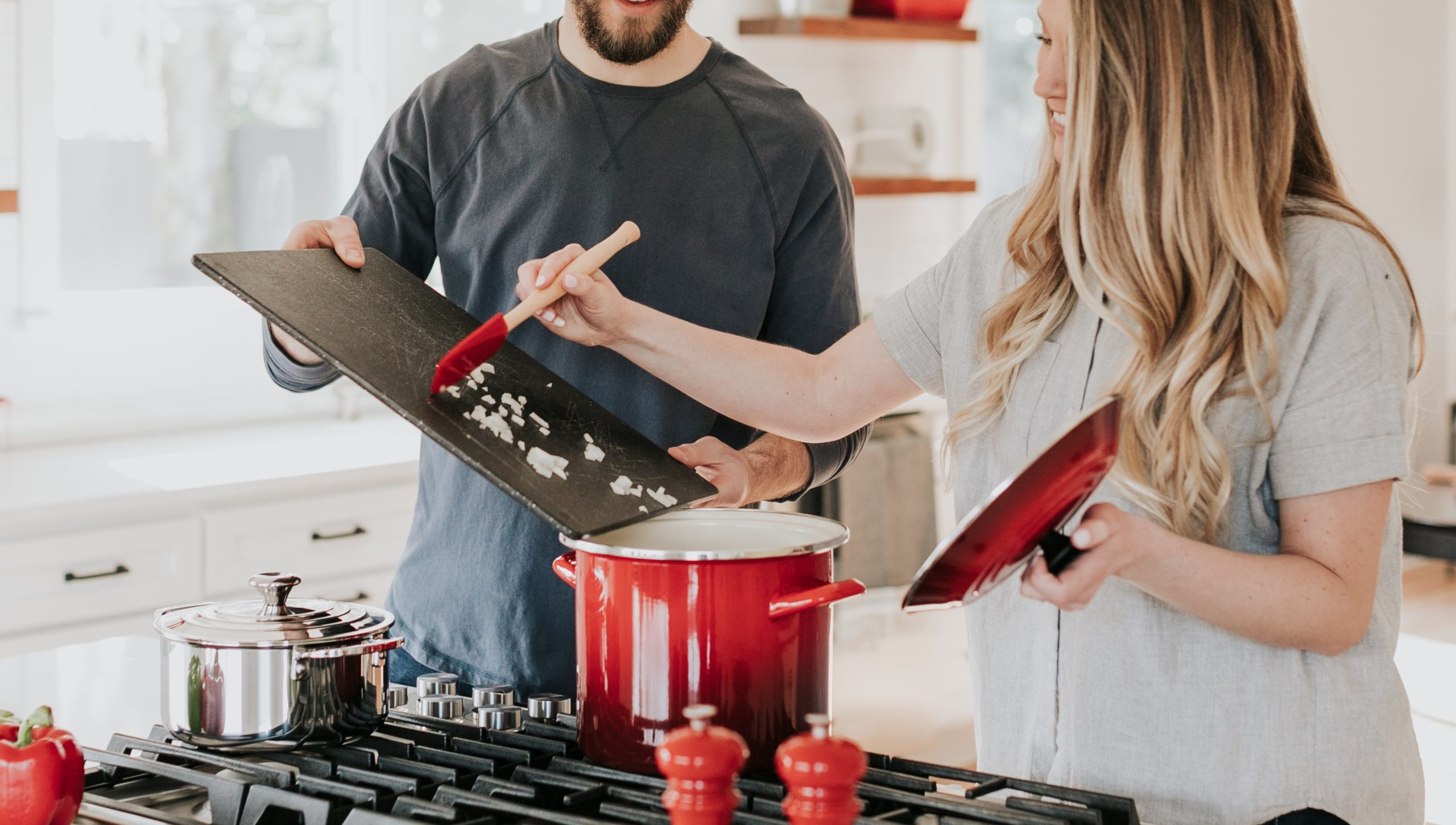 Two people cooking together - the man is holding a cutting board while a woman scrapes onions off of it into a dutch oven