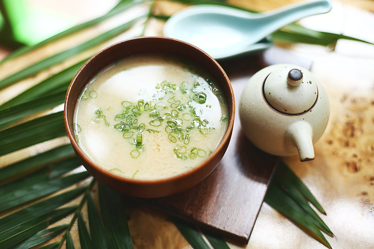 wooden bowl of miso soup with a tea pot nearby